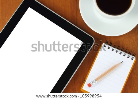Touch screen device, notepad, pencil and cup of coffee on wooden background