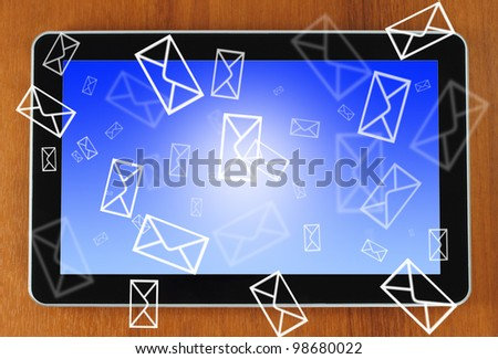 Touch screen device on wooden background with letters