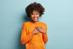 Touched beautiful smiling Afro American girl keeps palms on heart, expresses appreciation, pleasure and gratitude, wears orange sweater, models over blue background. Confession in love concept.