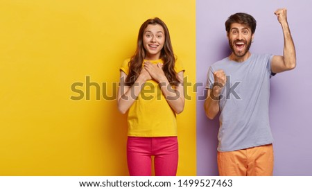 Touched pleased young European woman keeps palms on chest, gets pleasure from hearing heart warming words, overjoyed man shouts yes and clenches fists, stand together against two colored background