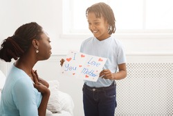 Touching Moment. African kid showing greeting card with I Love You, Mother text to her mom
