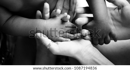Touching moment, touch of the hand of a small child and an adult woman. Mother and child, adoptive children, adoption. A white woman and a dark skinned child. Interracial relations, multiracial family Foto stock ©