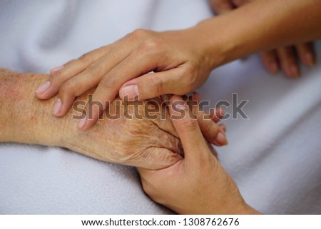 Touching or holding hands, asian senior or elderly old woman placed on a blue cloth with love, care, encourage and empathy.