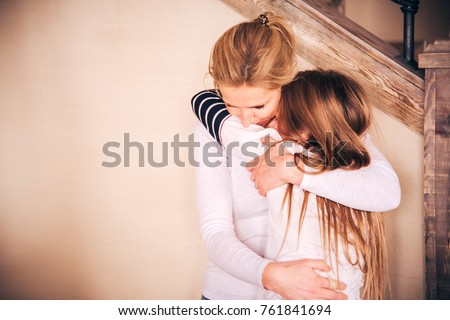 Touching portrait image of loving motherly hug. Mother showing her affection and love towards her beloved teenage daughter through warm tightly embrace. Happy Christmas time or mothers day background
