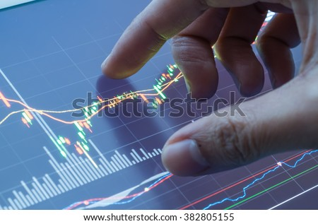 Touching stock market graph on a touch screen device. Closed up shot.