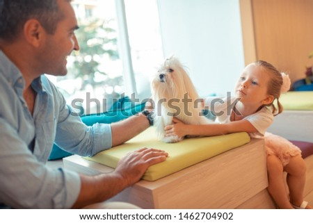 Touching their white fluffy dog. Blonde appealing daughter talking to daddy and touching their white fluffy dog #1462704902