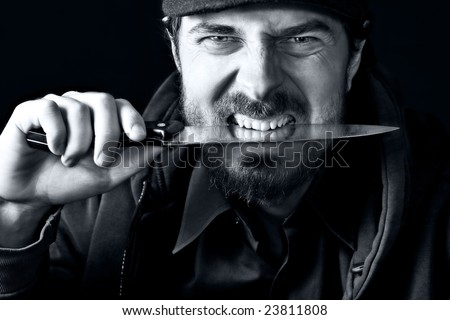 Tough angry guy biting from sharp knife