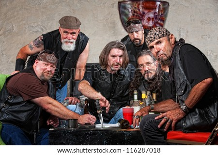 Tough group of Caucasian biker gang members with weapons