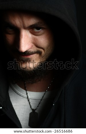 Tough guy grinning in the shadow of his hood