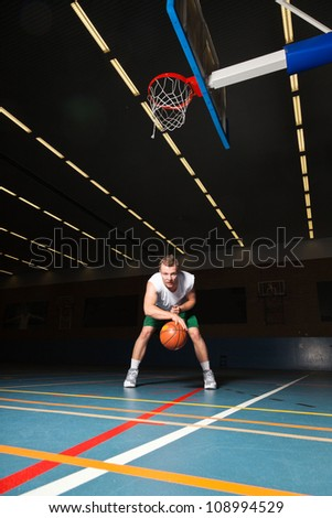 Tough healthy young man playing basketball in gym indoor. Wearing white shirt and green shorts.