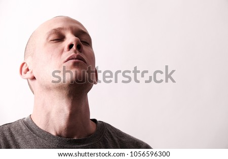 Tough looking man takes a deep breath with the head backwards, celebrates freedom, success and joy in life. Copy space for text on white background. #1056596300