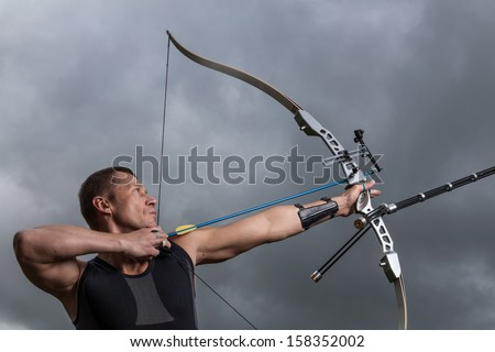 Tough man with bow and arrows, close up with cloudy sky at background.