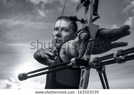 Tough man with bow and arrows, close up with cloudy sky at background. Monochromatic