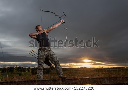 Tough man with bow and arrows during dramatic cloudy sunset.