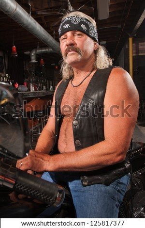 Tough middle aged man on motorcycle in bar