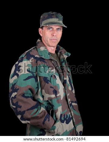 Tough middle aged solider with hands in his pockets isolated on black.