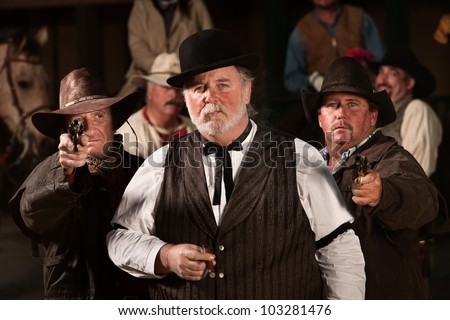 Tough old west gambler with armed friends