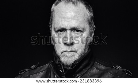 Tough, serious bearded man in leather jacket on black background (black and white).