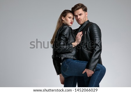 Tough young man embracing and protecting his girlfriend while holding her leg, both wearing leather jackets and jeans, standing on gray studio background #1452066029