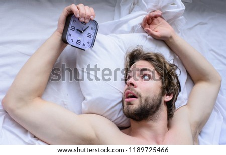 Toughest part of morning simply getting out of bed. Get up early morning tips. Oversleep problem. Man unshaven surprised shocked face lay pillow alarm clock top view. Guy missed alarm clock ringing.