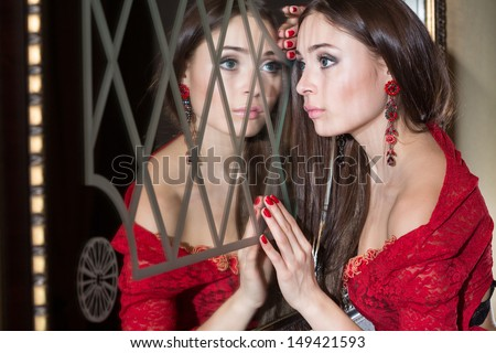 Toung girl in the red dress looks in the mirror #149421593