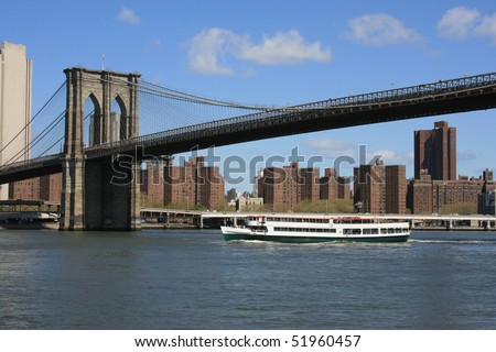 Tour boat passing under the Brooklyn Bridge, New York.