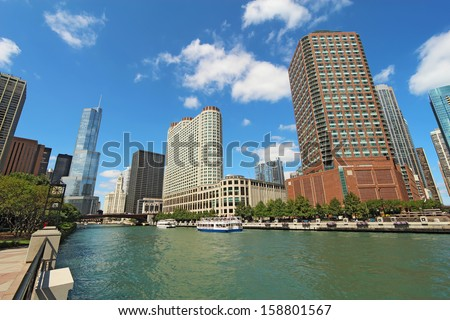 Tour boats and the city skyline along the Chicago River in Chicago, Illinois against a bright blue sky with white clouds