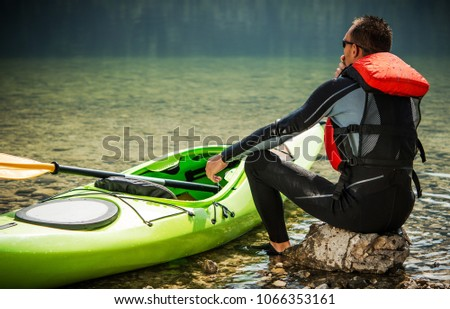 Tour Kayaker and the Lake. Caucasian Men in His 30s and His Green Plastic Kayak. Water Recreation Theme. #1066353161