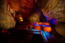 Tour path through Indiana underground cave with waterfall lite by blue and orange lights
