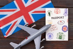 Tourim flight to the Grean Britain concept. Vacation in the United Kingdom. Composition of the UK flag, passport and toy airplane.