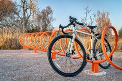 touring bike parked in  colorful helix bike racks along a trail in Fort Collins, Colorado - outdoor activity and bike commuting concept