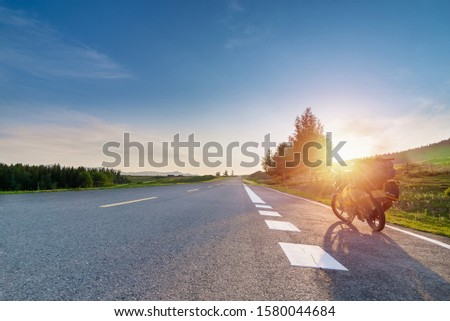 Touring motorcycle with baggage and sunbeams parked on asphalt road which passing through grassland with white painting line #1580044684
