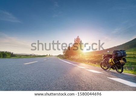 Touring motorcycle with baggage and sunbeams parked on asphalt road which passing through grassland with white painting line #1580044696