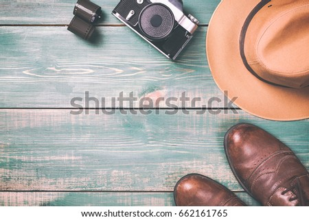 Photo of Tourism and travel concept. Vintage camera with film, brown shoes and fedora hat on green wooden background. Toned image and free space