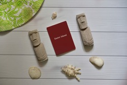 Tourism and travel concept with passport, green white hat, two moai statuettes from Easter Island and four sea shells on a wooden background. Flat lay.