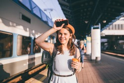 Tourism and travel in the summer. Vacations for the student. Work and travel. Caucasian young woman drinks coffee on the platform of the railway station against the background of the train.