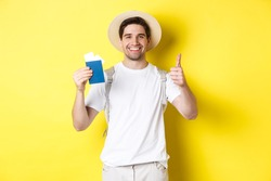 Tourism and vacation. Satisfied male tourist showing passport with tickets and thumb up, recommending travel company, standing over yellow background