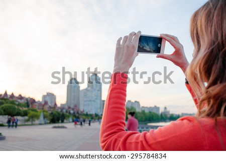 Tourism concept. Young woman with beautiful hair taking photo on smartphone while walking by the city.