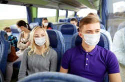 tourism, healthcare and pandemic concept - couple with group of passengers or tourists wearing face protective medical mask for protection from virus disease in travel bus