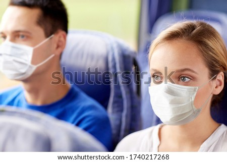 tourism, healthcare and pandemic concept - young woman wearing face protective medical mask for protection from virus disease sitting in travel bus or train