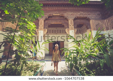 Tourism in Morocco, handsome girl walking in a garden in the square of Marrakech, Morocco