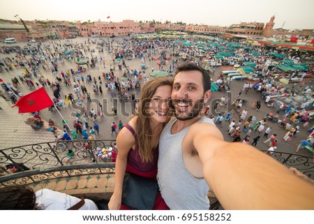 Tourism in Morocco. Tourist couple take selfie photo in the old main square Jamaa el-Fna market Marrakech at sunset. concept of travel, discover and culture. tourists visiting world famous landmarks
