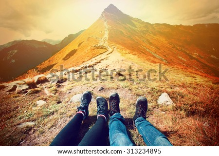 Tourism in mountains. A couple of tourists rest on the mountain path. Nature in mountains at autumn.