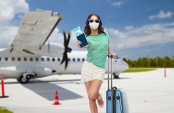 tourism, pandemic and health care concept - teenage girl in sunglasses wearing face medical mask for protection from virus disease with travel bag and air ticket over plane on airfield background