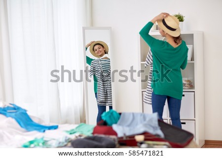 tourism, people and luggage concept - happy young woman packing travel bag at home or hotel room and looking to mirror