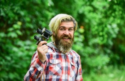 Tourism summer vacation. Hobby and leisure. Observing nature. Guy explore environment. Man ornithology expedition in forest. Man observing nature. Hipster tourist holds binoculars nature background.