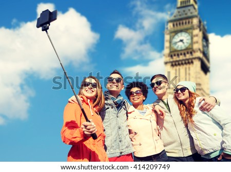 tourism, travel, people, leisure and technology concept - group of smiling teenage friends taking selfie with smartphone and monopod over london big ben tower background