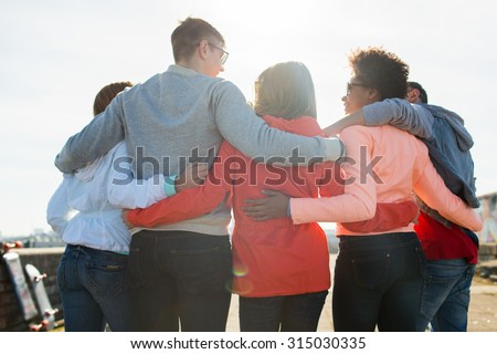 tourism, travel, people, leisure and teenage concept - group of happy friends hugging and talking on city street from back