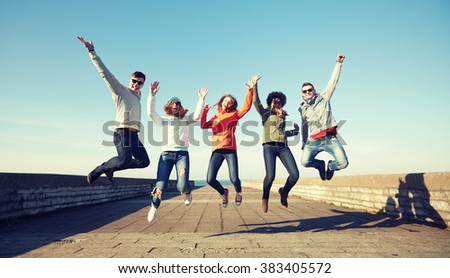tourism, travel, people, leisure and teenage concept - group of happy friends in sunglasses hugging and laughing on city street #383405572