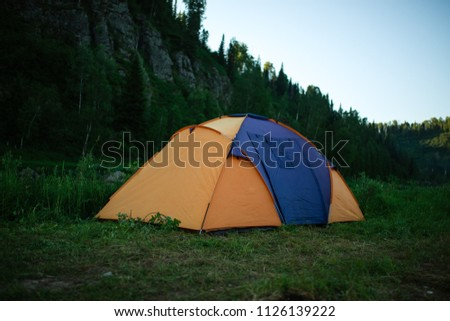 tourism, travel, tourism, tourism and the concept of active people's they, creating a tent in the open air. to collect a tent in nature. Camping and tent under a pine forest at sunset. #1126139222